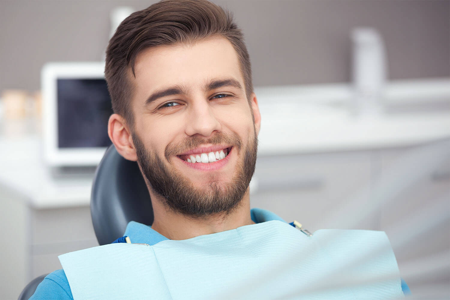 A good looking man smiling while sitting at our dental chair