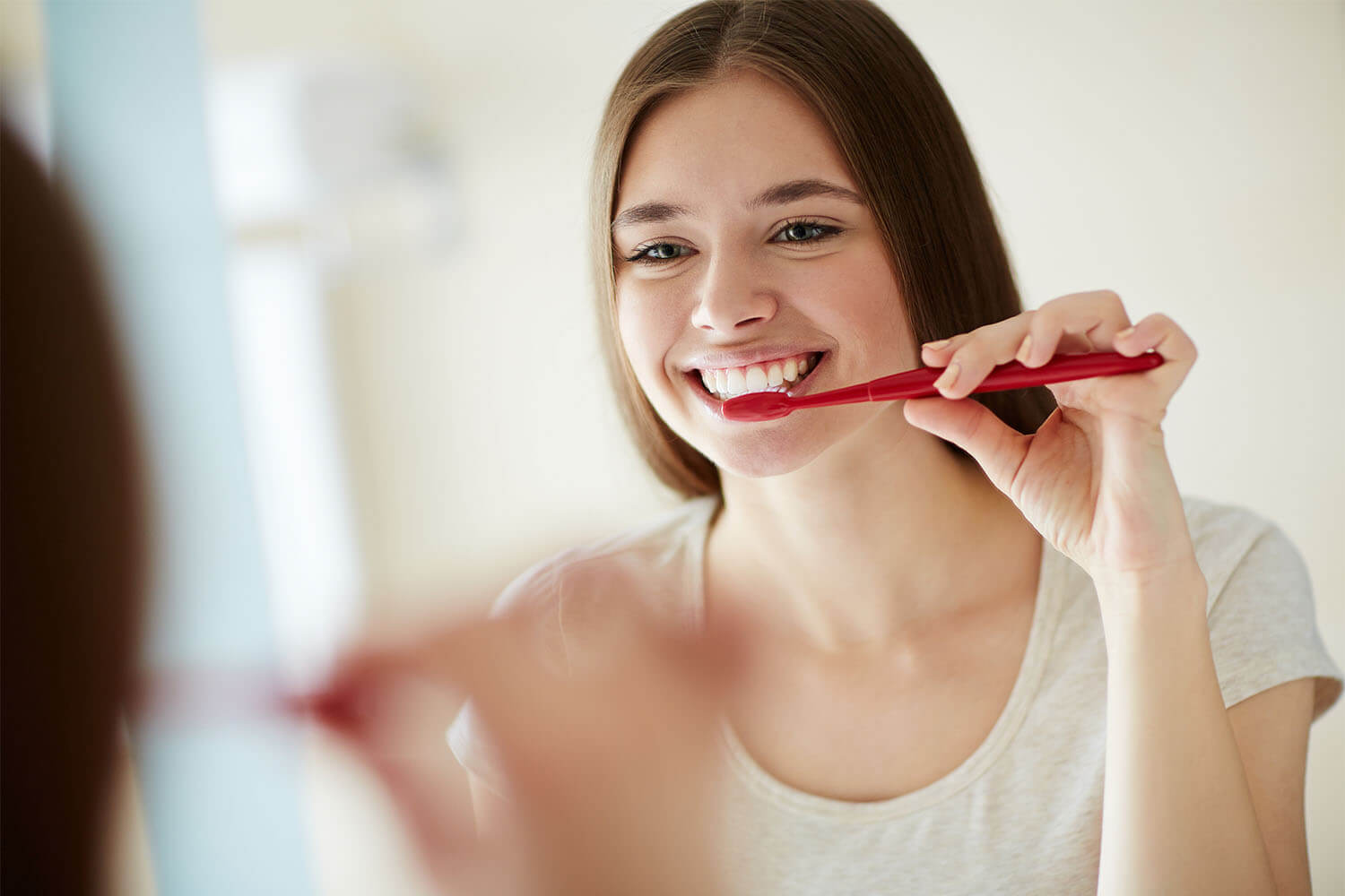A smiling woman brushing her teeth