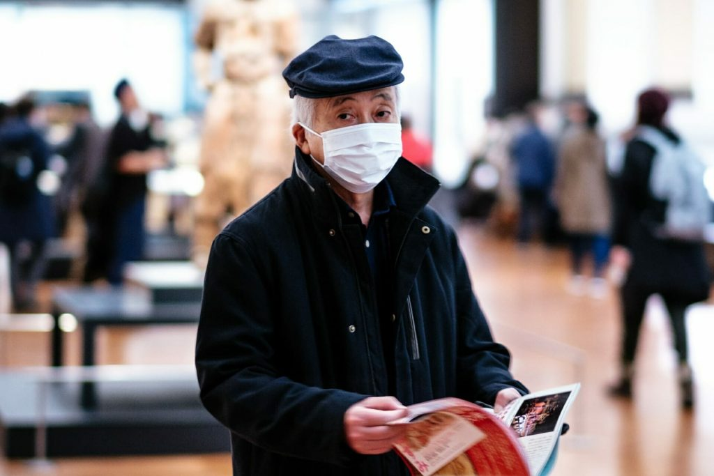 An old man wearing face mask and holding a magazine